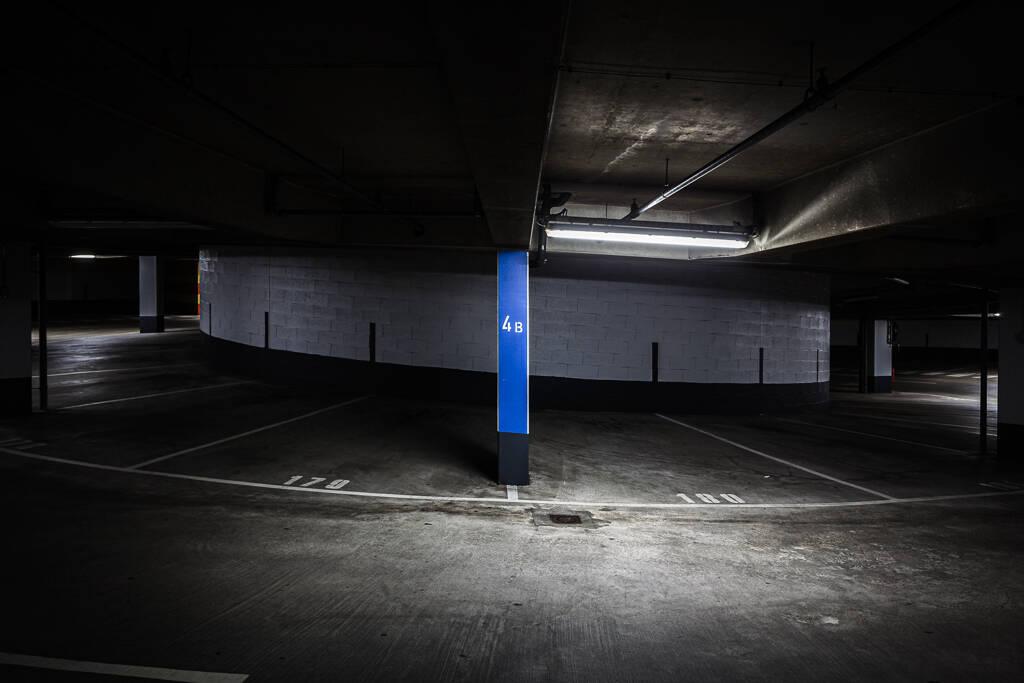 Entre deux places d'un parking souterrain mal éclairé.
