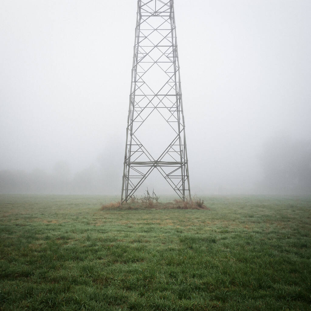 Base d'un pylône électrique dans le brouillard.