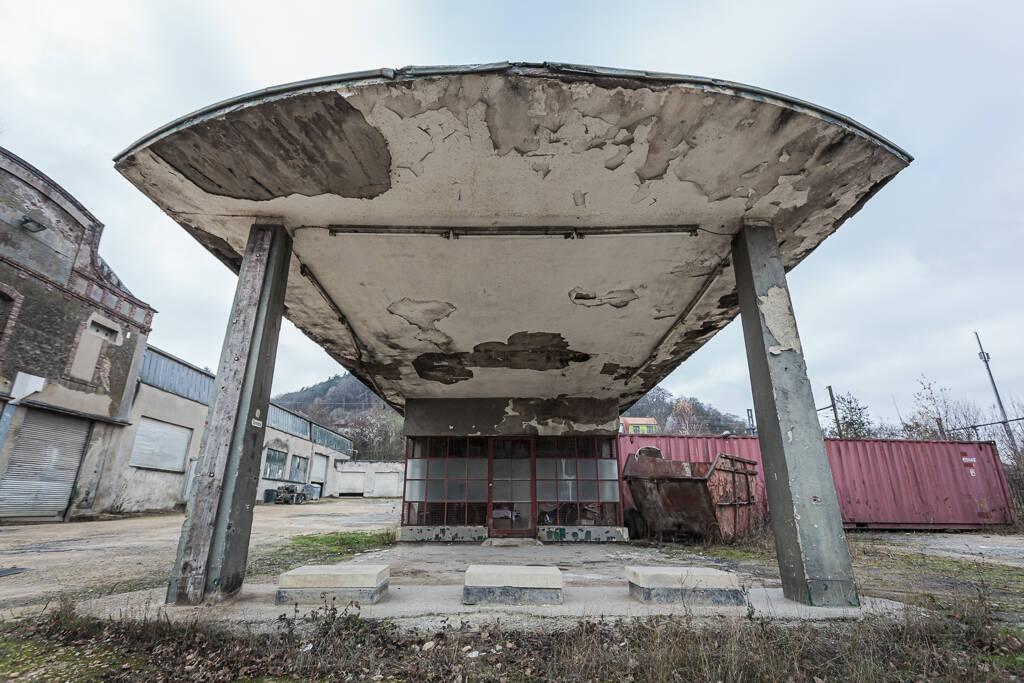 Plan large sur une ancienne station service à l'abandon.