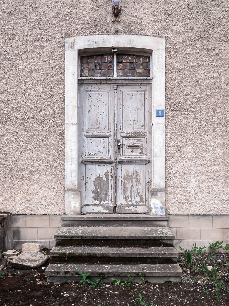 Porte d'une ancienne école primaire à l'abandon.