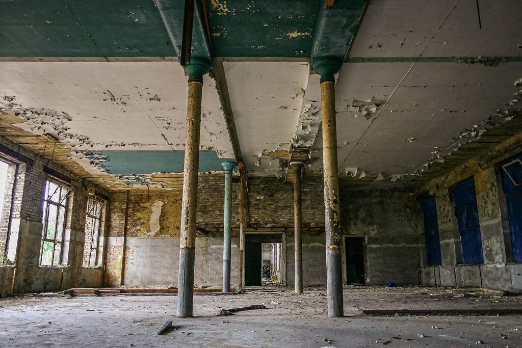 Perspective sur une grande salle délabrée et ses colonnes.