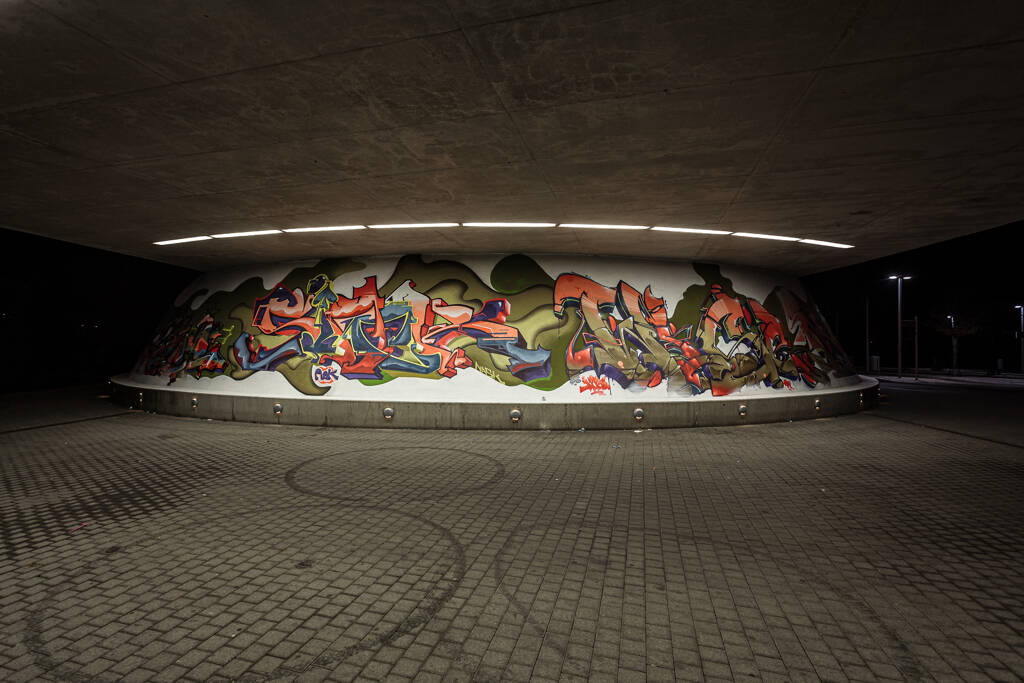 Grand angle sur les graffiti recouvrant le pied d'un pont à Lamadelaine...