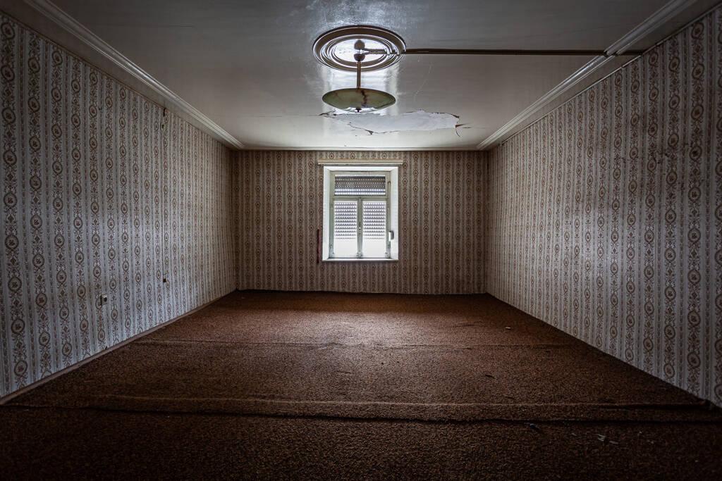 Perpective sur une chambre aux murs de travers décorés de papier peint à motifs...