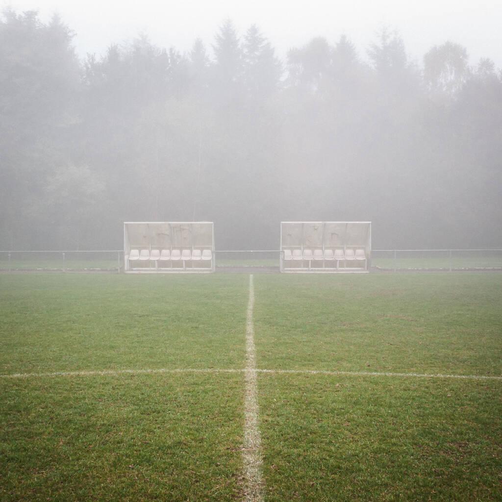 Vue dans le brouillard d'un terrain de football et de ses bancs de touche...