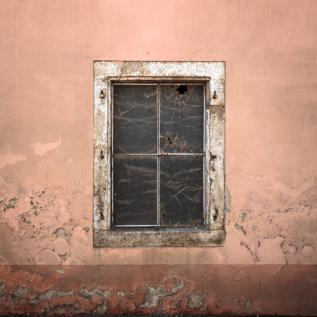 Vieille façade de ferme avec sa fenêtre aux carreaux brisés.