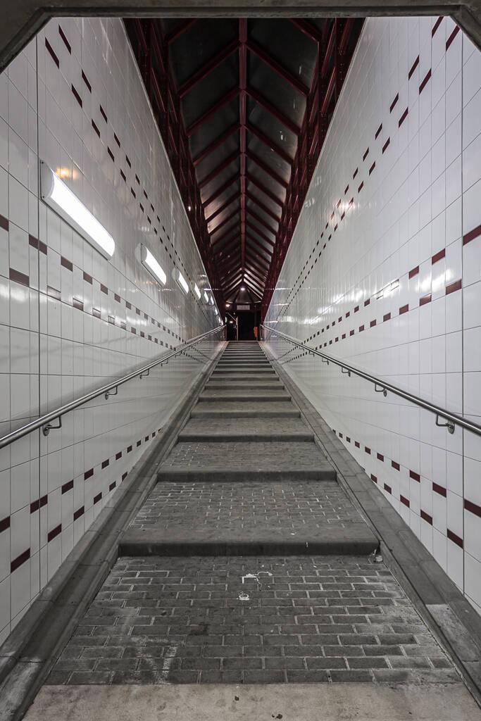 Perspective de nuit sur une rampe menant à un quai de gare.