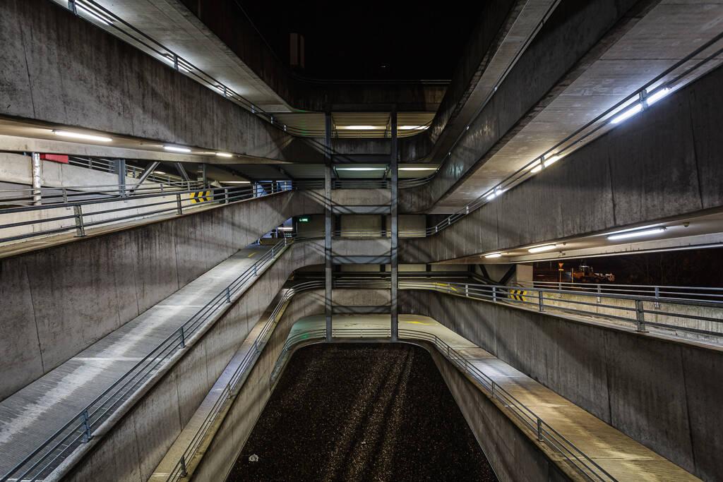 Perpective sur les rampes de parking éclairée la nuit.