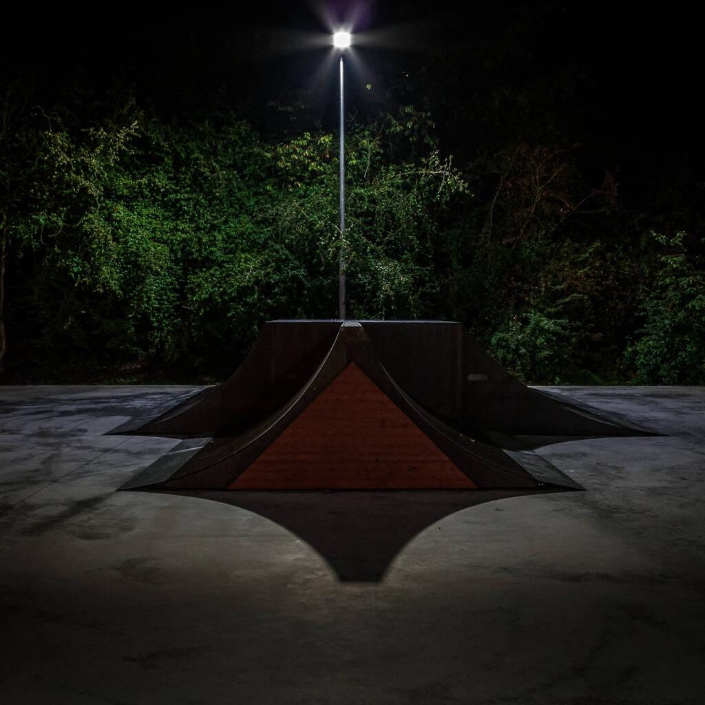 Rampe d'un skatepark éclairée la nuit.