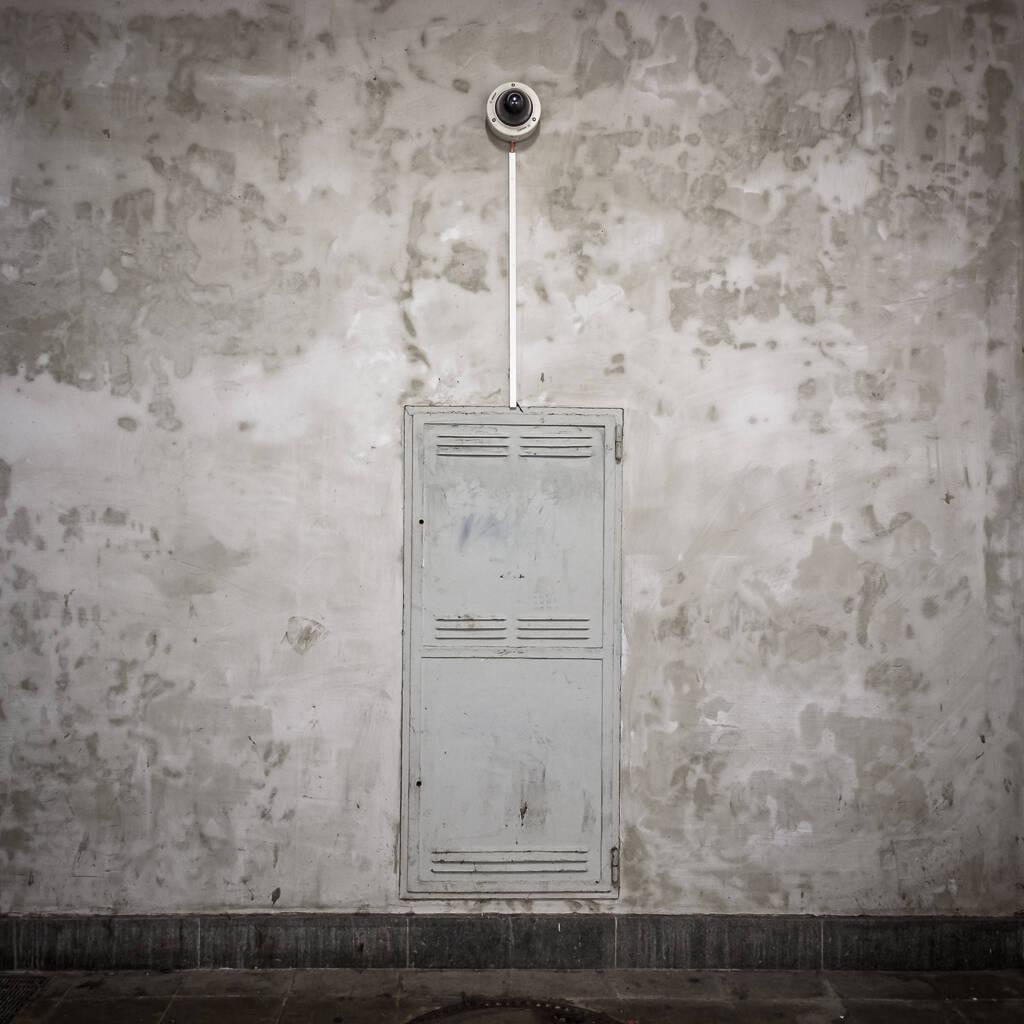 Caméra de surveillance suspendue au fond d'un tunnel de gare.