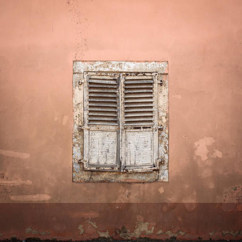 Vieille façade de ferme avec sa fenêtre occulté par des volets.